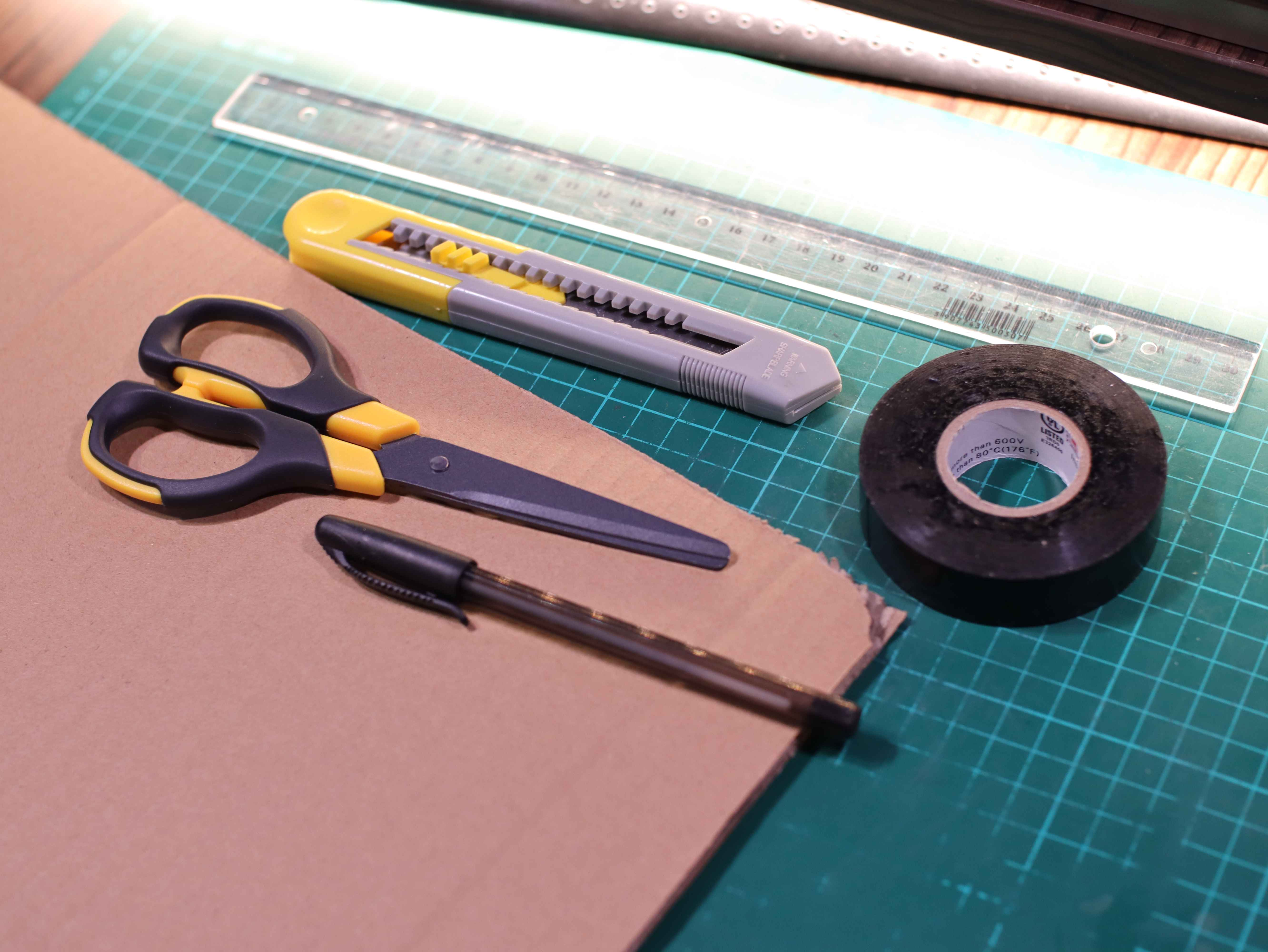 Preparation of materials for making an ASG battery from cardboard. Scissors, knife, black tape, pen, and cardboard.
