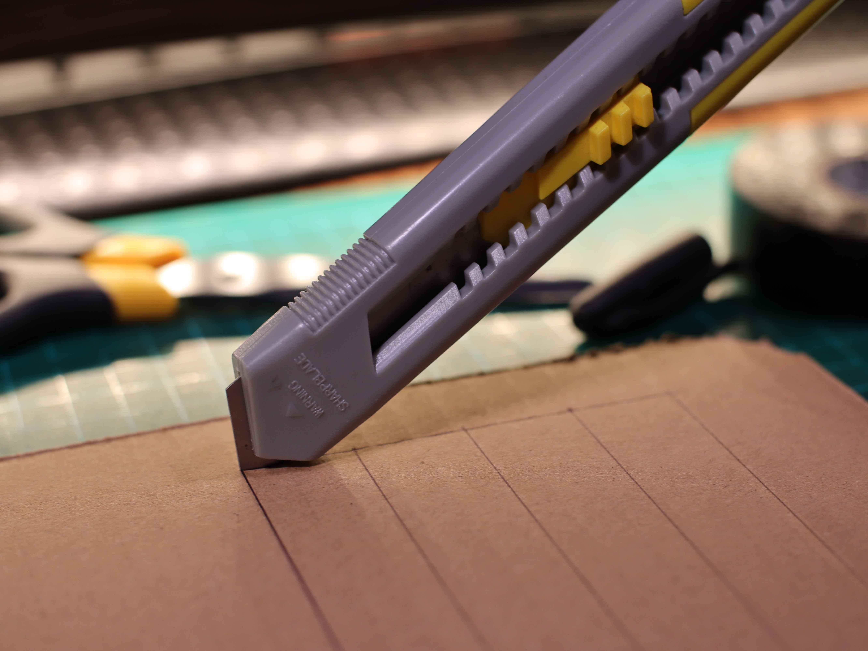 Wycinanie akumulatora airsoft z kartonu. Nóż tnie po wyrysowanych liniach modelu.