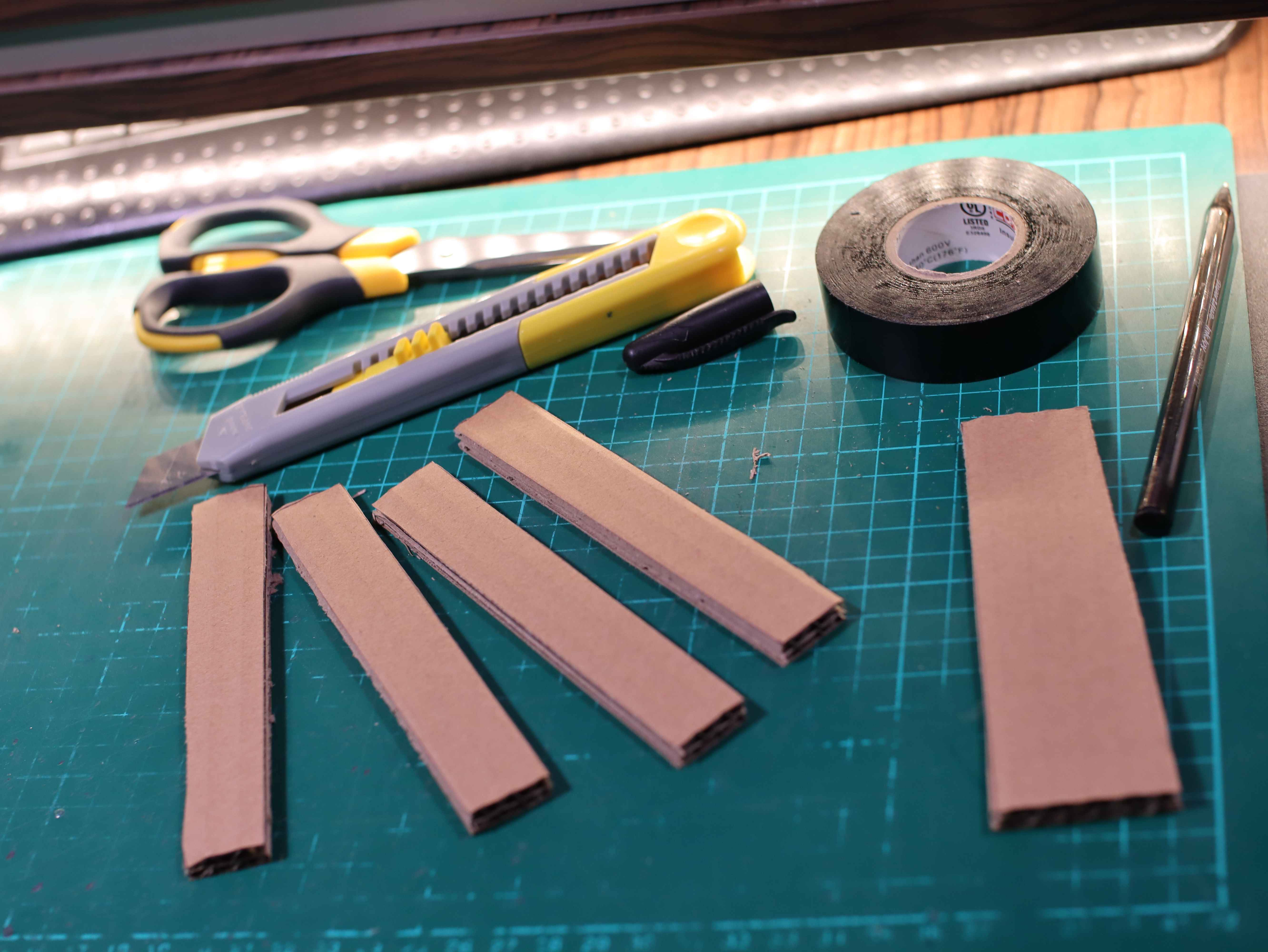 Airsoft battery elements cut out of cardboard. The knife, scissors, pen, electrical tape are on the green service mat.