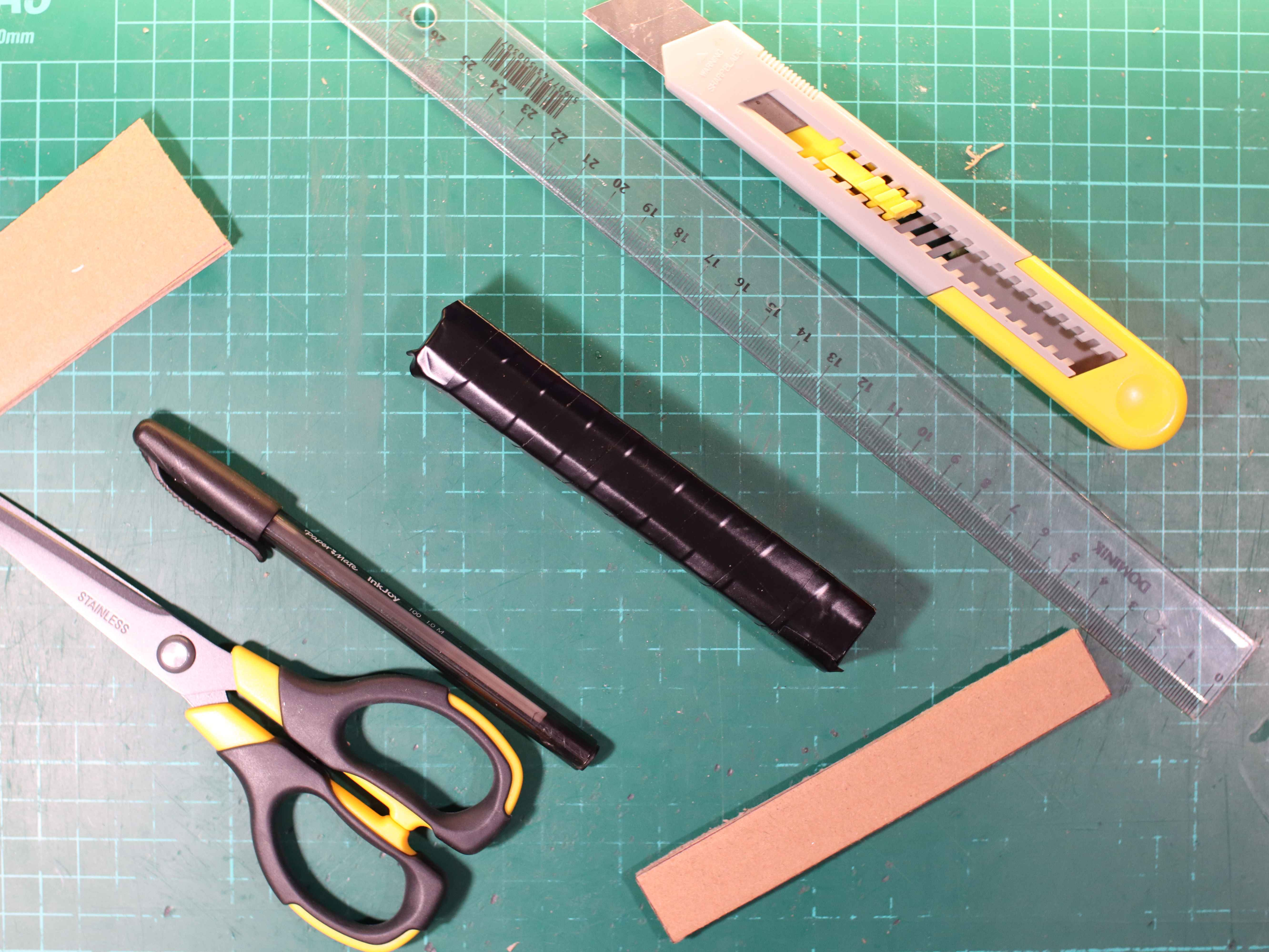 Cardboard battery covered with black insulating tape. Scissors, a knife, a pen, a ruler are on the green service mat.