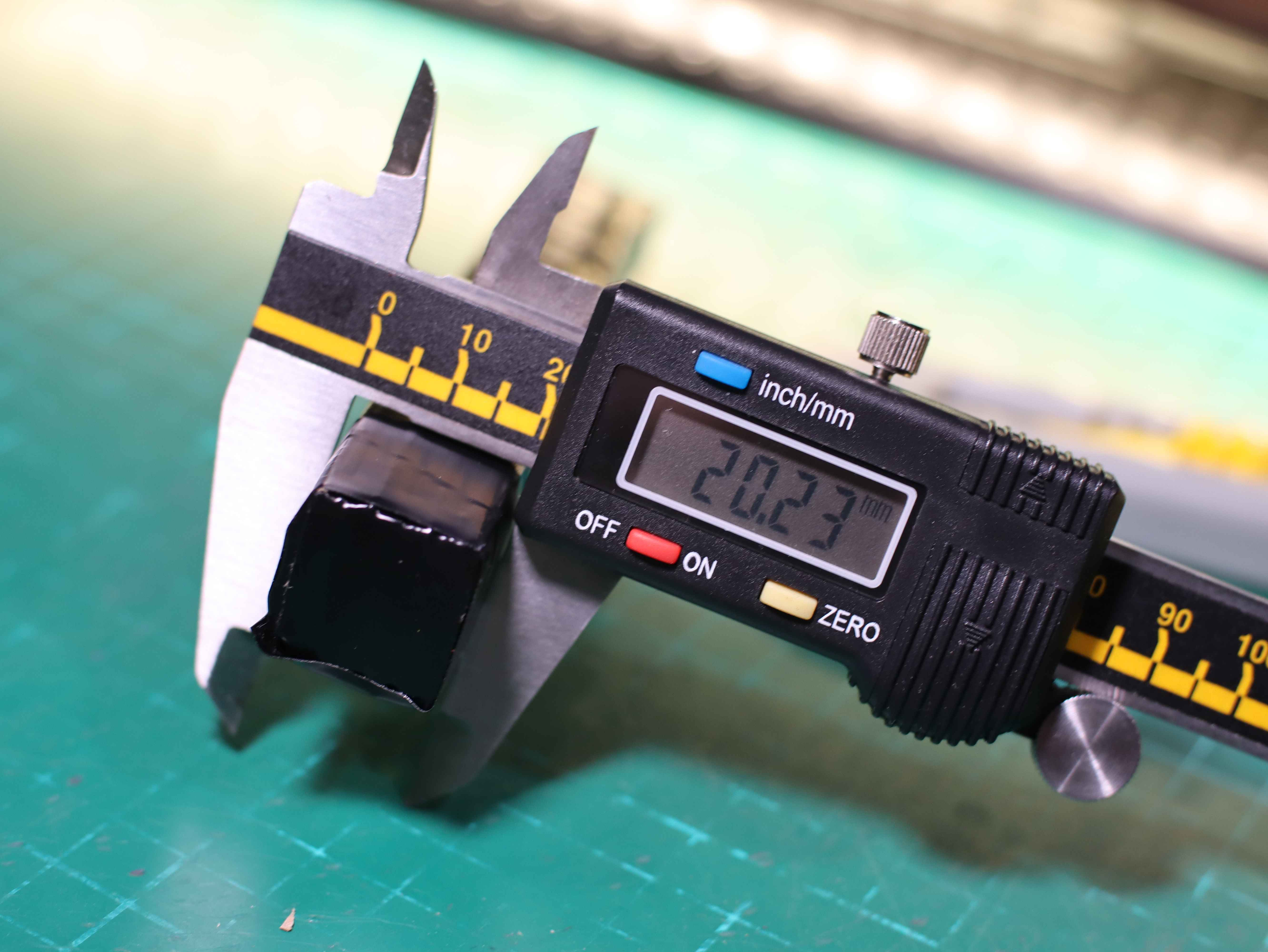 Airsoft battery thickness measurement from cardboard. Caliper, cardboard battery, covered with black insulating tape.