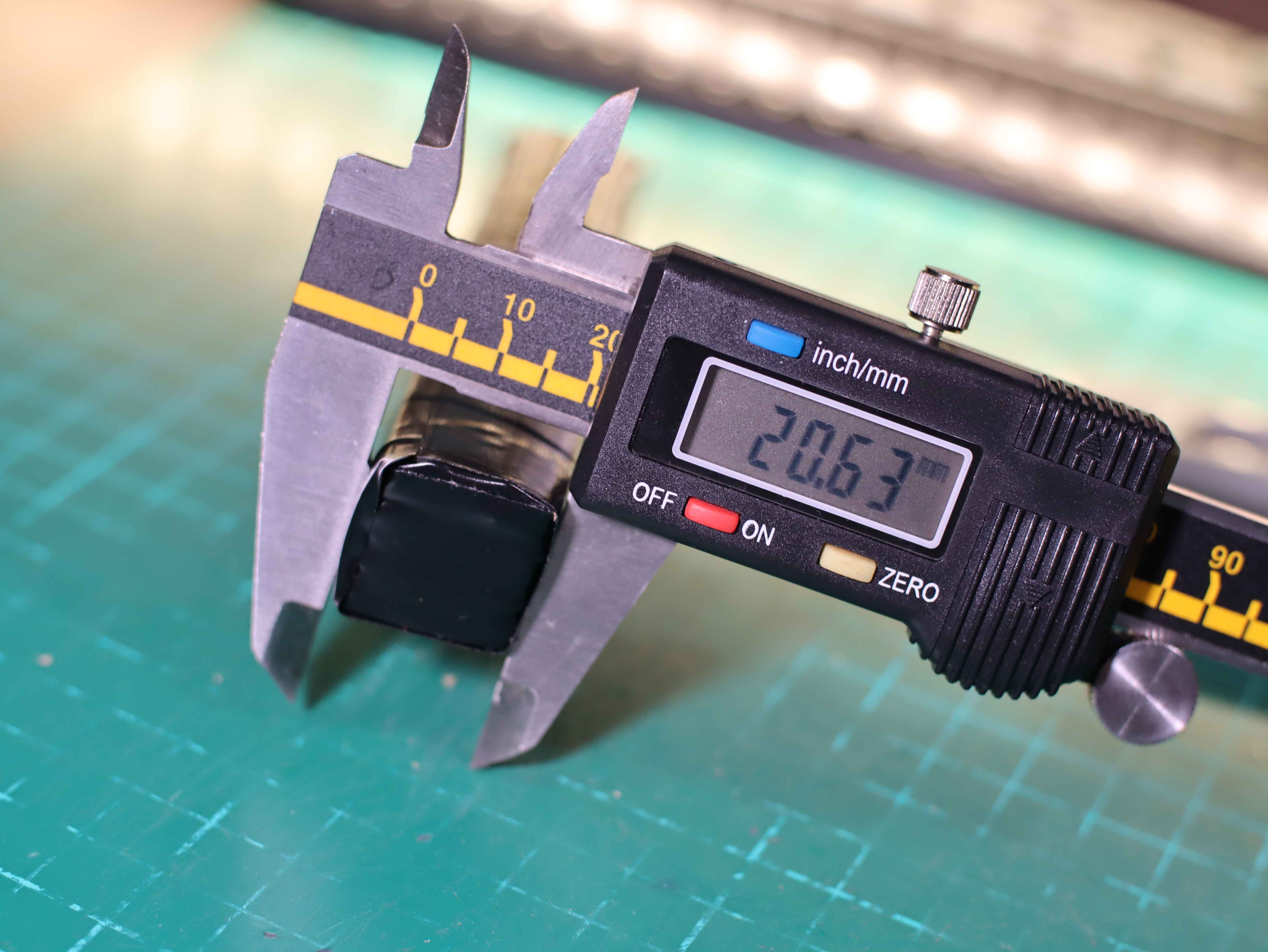 Re-measure the thickness of the battery from the cardboard. Electronic caliper and model covered with insulating tape.