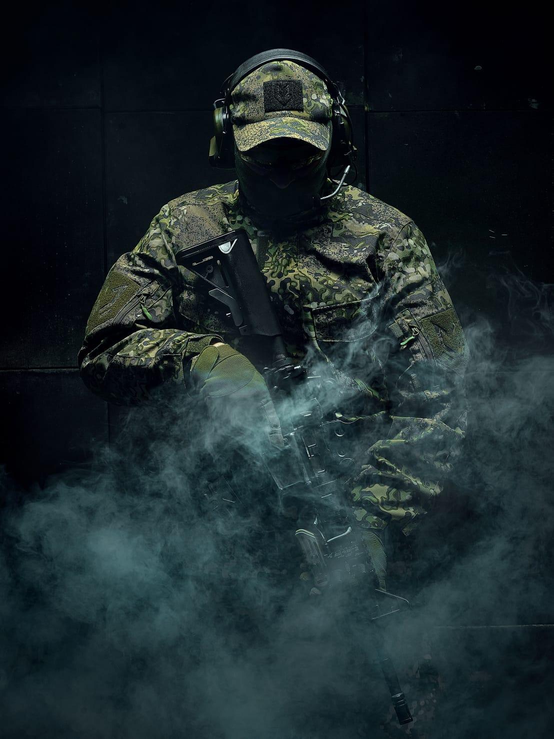 mężczyzna w mundurze w kamuflażu MAPA od Maskpol; trzyma replikę airsoft; stoi w dymie