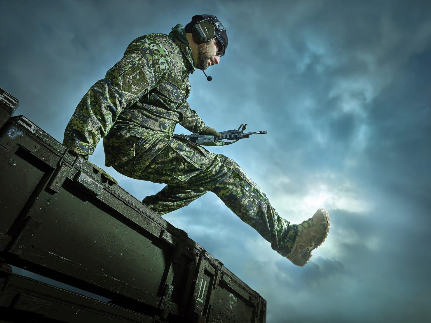 mężczyzna w mundurze w kamuflażu MAPA od Maskpol skacze przez płot; trzyma replikę ASG