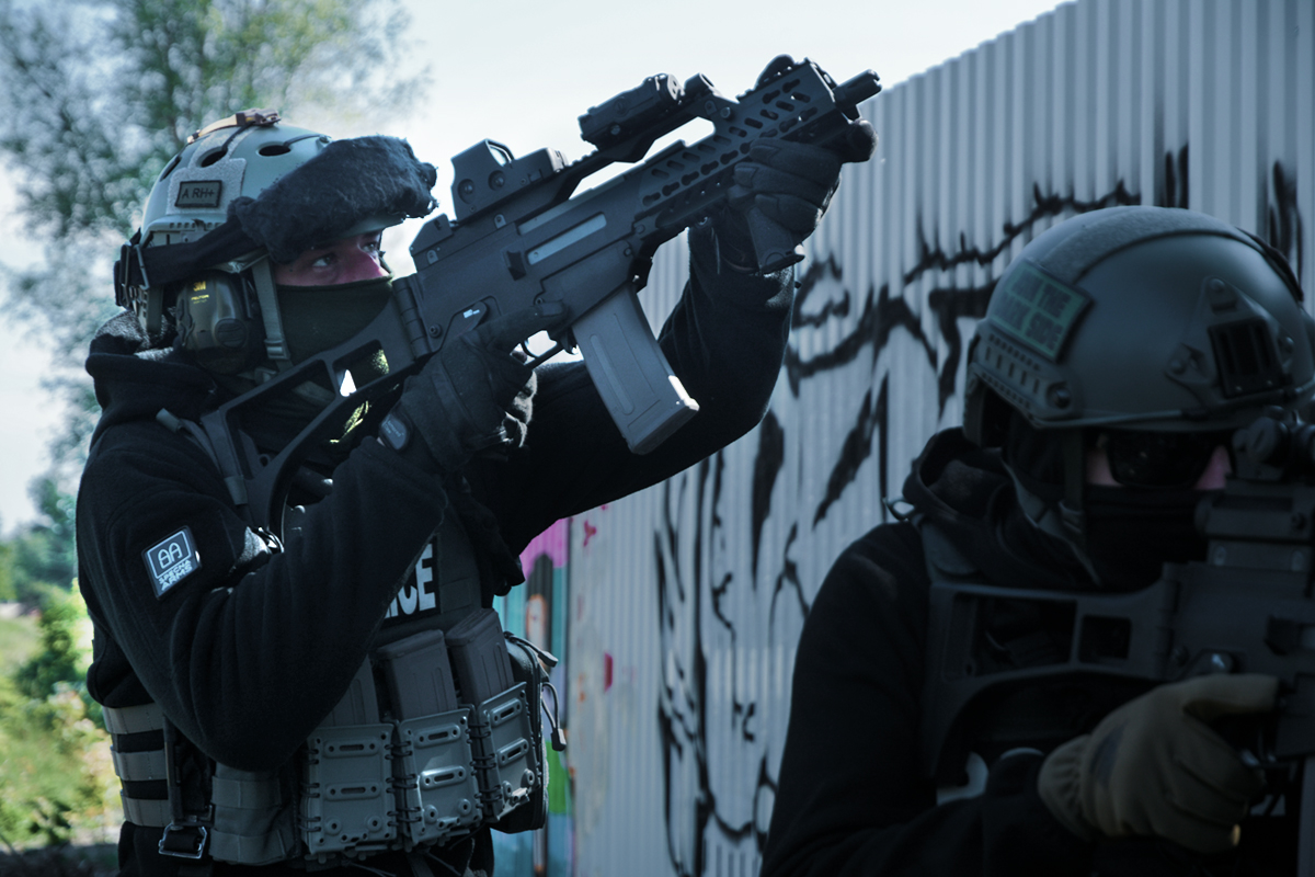 mężczyźni w mundurach , kaskach i z replikami airsoft; pod kaskiem jest kominiarka; napis police na kamizelce