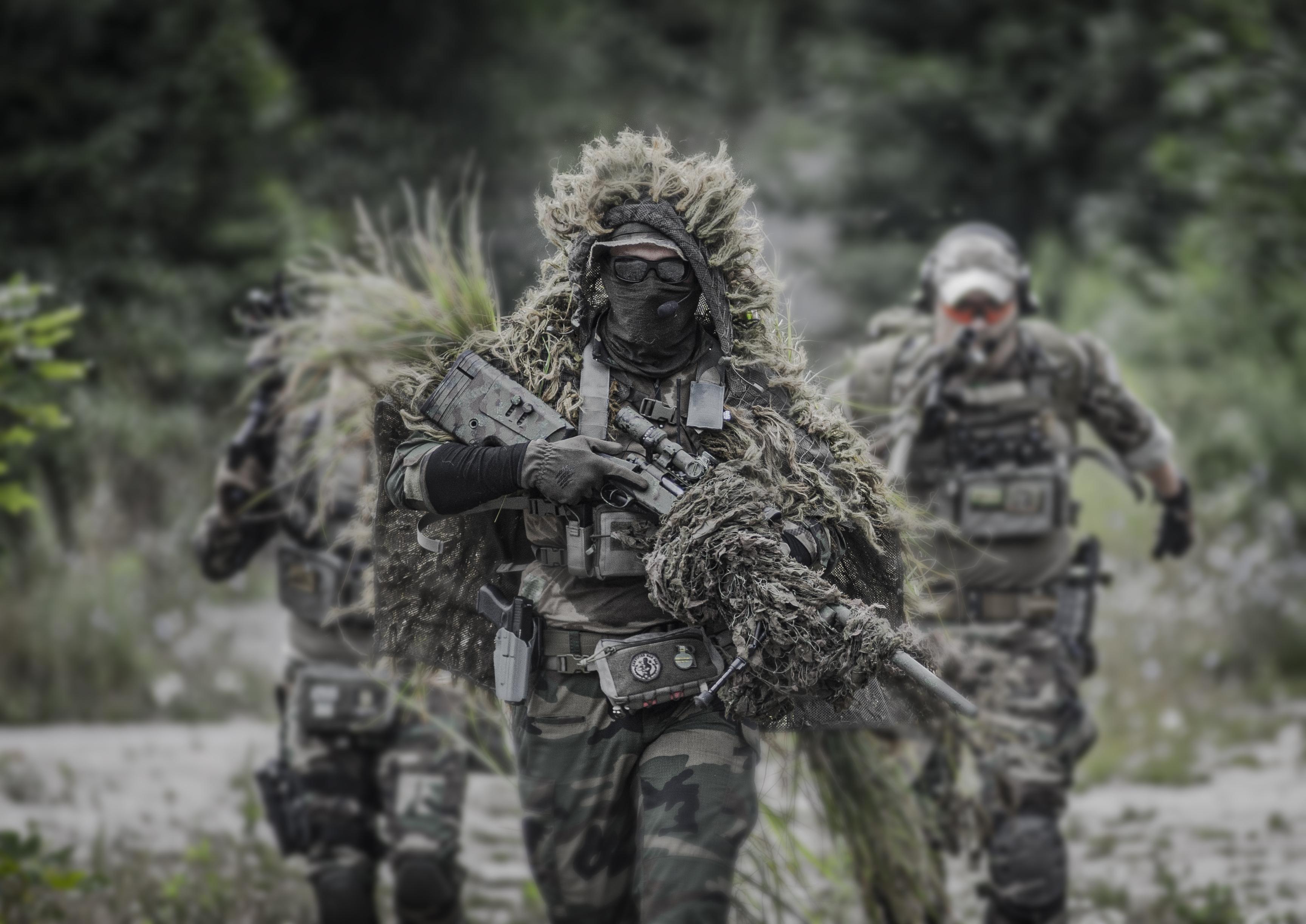 mężczyźni w kamuflażach z replikami ASG idą
