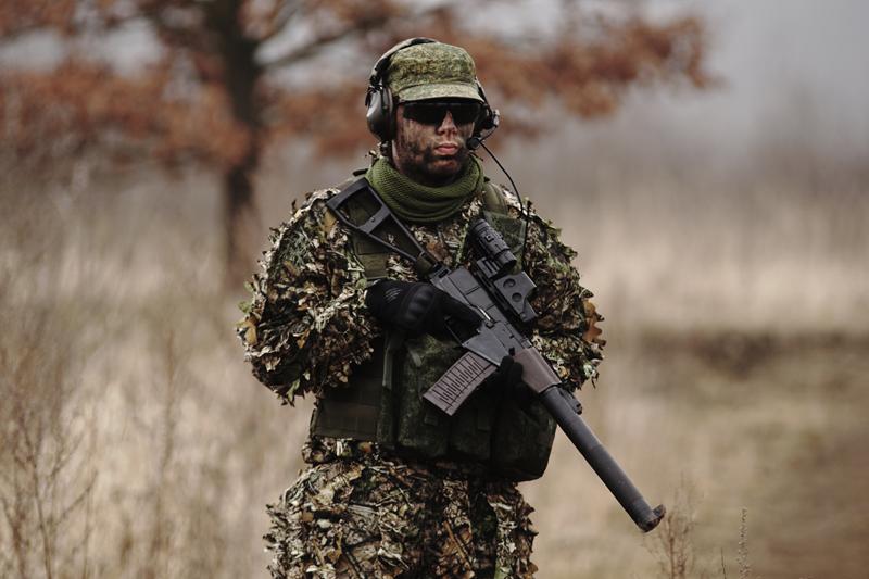 un homme en uniforme avec des tenues de camouflage et des lunettes de protection tient une réplique d'airsoft