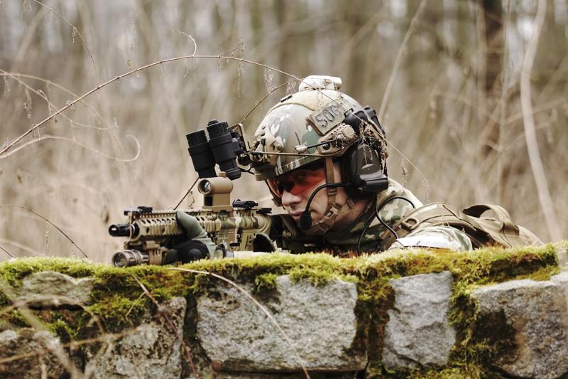 un joueur d'airsoft portant un casque et des lunettes de protection vise une réplique, cachée derrière un mur.