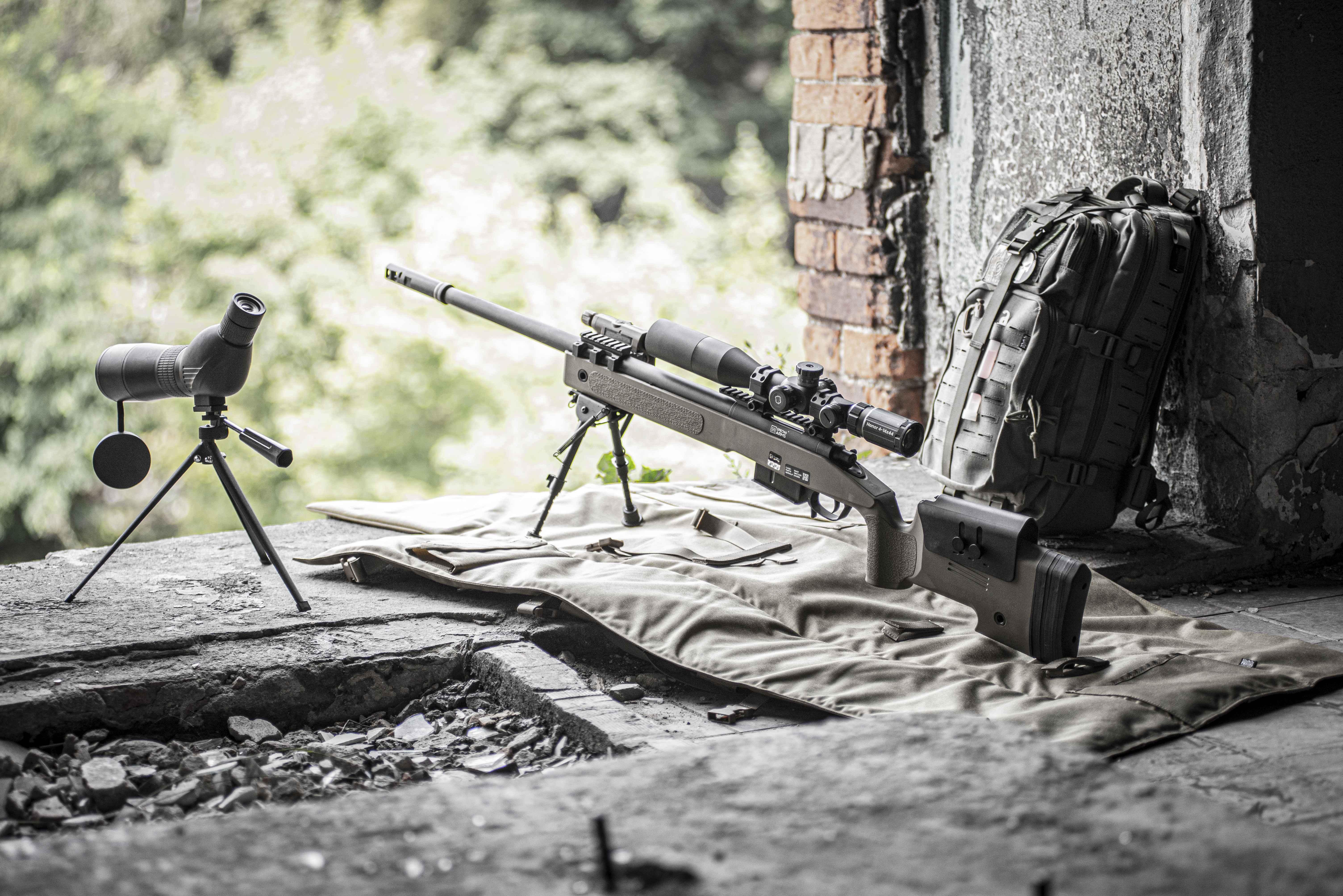réplique d'un fusil de sniper de Specna Arms en vert olive, fenêtre dans un bâtiment abandonné ; lunette de visée