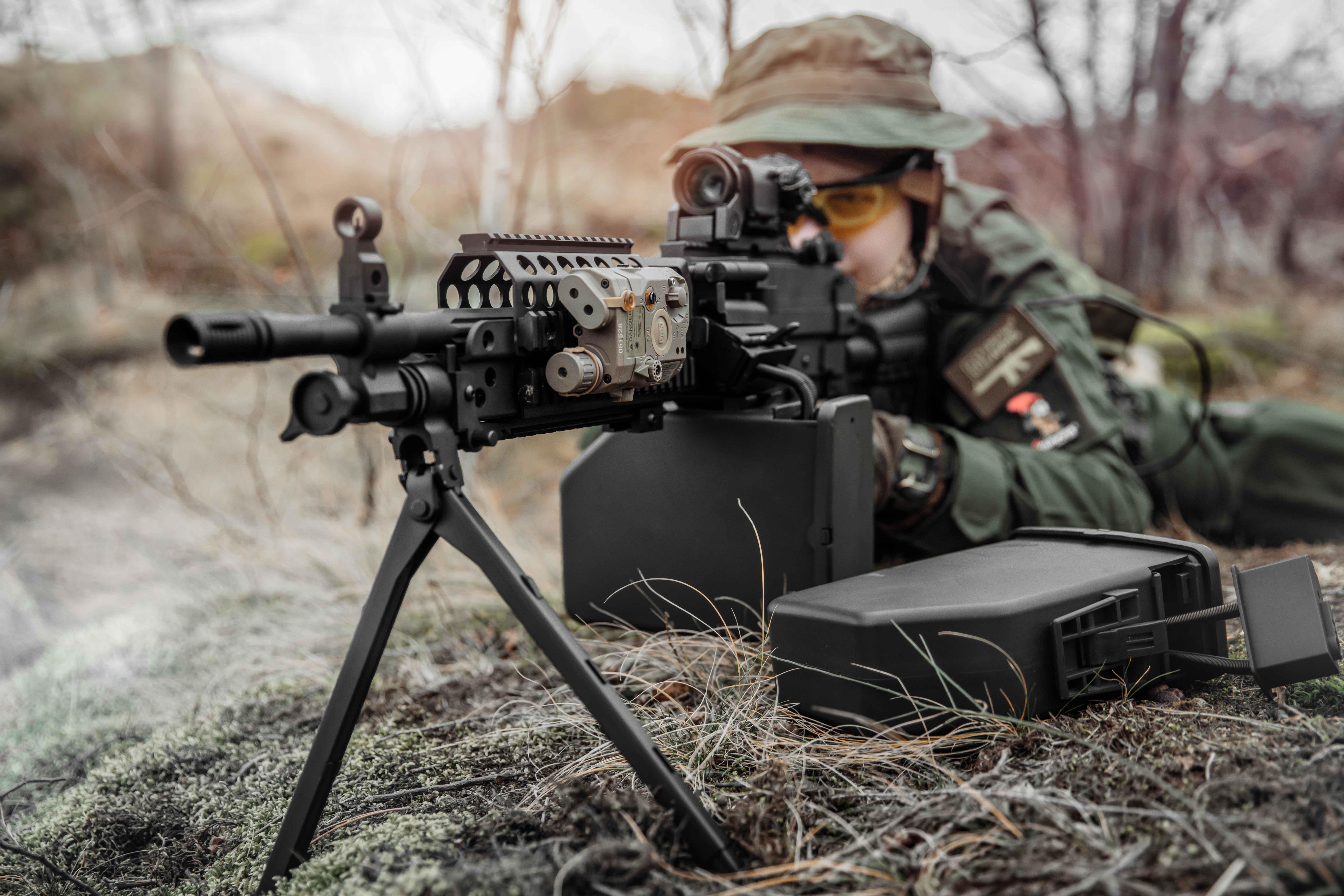 réplique d'une mitrailleuse de l'arme Specna ; homme en uniforme visant la réplique ; bipod