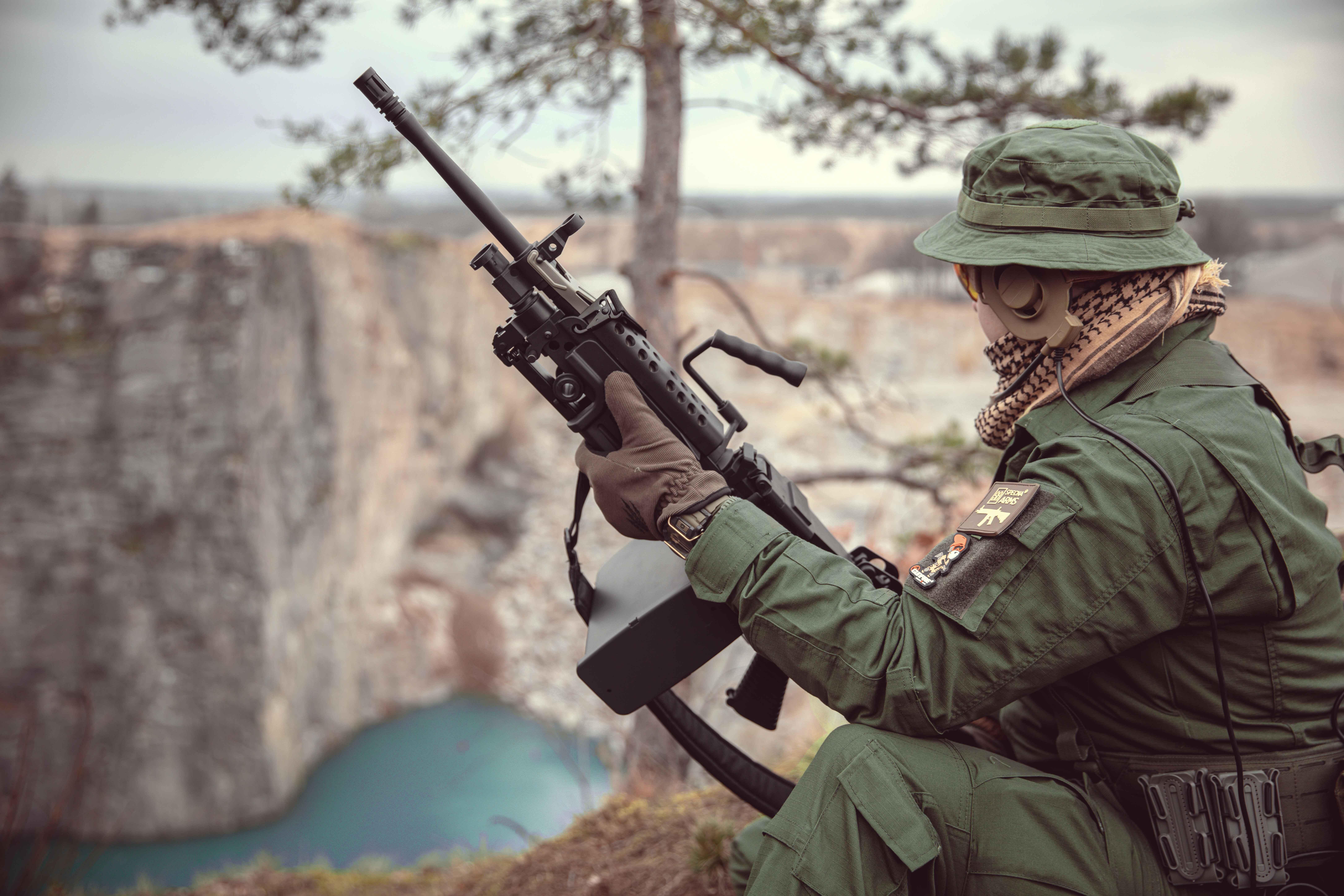 Réplique d'une mitrailleuse de l'arme Specna avec bipied plié ; homme en uniforme assis sur le bord